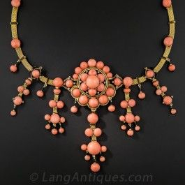 From late nineteenth century France comes this rare and ravishing Victorian era masterpiece featuring a collection of bright salmon colored ocean gems. The coral beads and buttons are arrayed over a fine 18K mesh necklace artfully accented with black enamel. A truly exemplary and stunning adornment. 16 inches in length, 3 3/4 inch centerpiece.