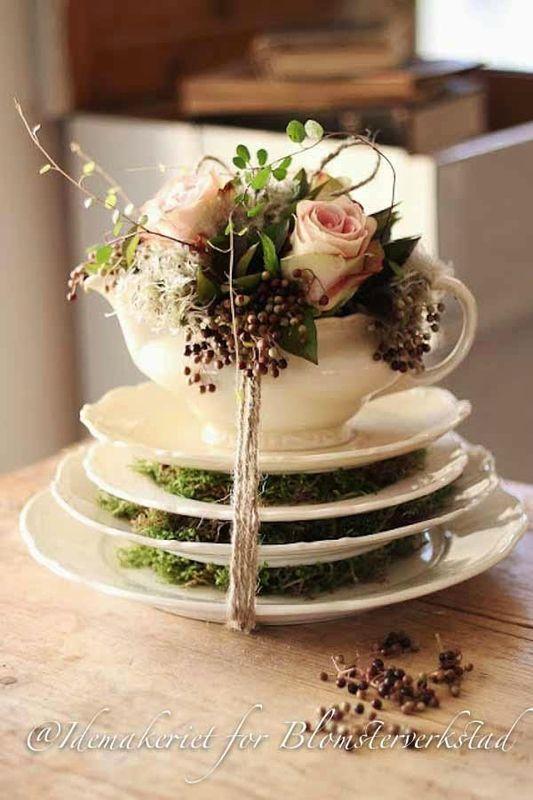 quelques assiettes à dessert, des fleurs, de la mousse pour un centre de table tout en poésie