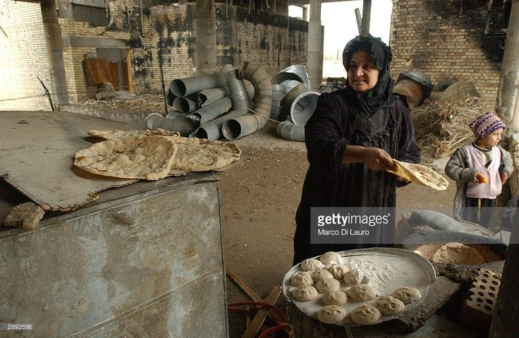 An Iraqi woman and child make bread in her house at a former Iraqi Air Force Base January 23, 2004 in central Baghdad, Iraq. Hundreds of Iraqi families now live in these abandoned government buildings rather than be homeless.