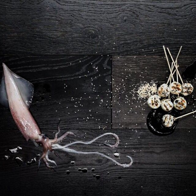 Squid lollipops with squid ink aioli and toasted sesame seeds.