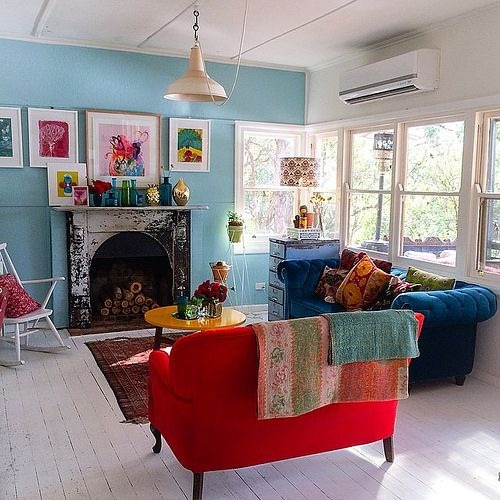 Red and blue sofa, turquoise walls, all that beautiful light and a yellow table! Wow. In artist Paula Mills home.