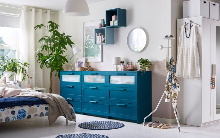 A bedroom in neutrals with three blue chest of drawers in a row. IKEA