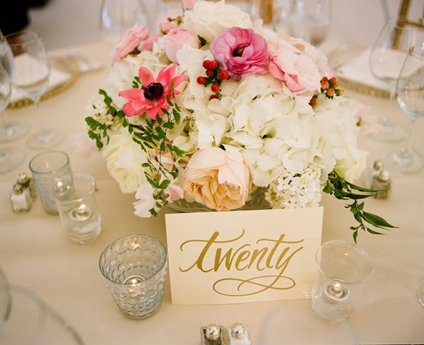 Fresh floral centerpiece with gold table numbers