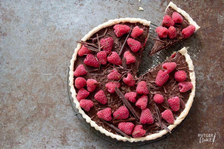 De romige chocoladeganache in deze chocoladetaart combineert goed met de frisse frambozen. De frambozenjam in de taart is op smaak gebracht met rozenwater.