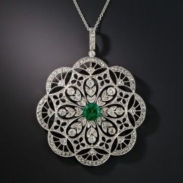 Rigorously and exquisitely detailed and hand fabricated platinum, this exemplary Edwardian era jewel, measuring 1 5/8 inches diameter, glitters with approximately 200 tiny rose-cut diamonds arrayed over an intricate doilyesque design centered with an intriguing, unusually deeply saturated, rich green round faceted emerald weighing 1.35 carats. A truly rare, ravishing, and resplendent Belle Époque jewel.