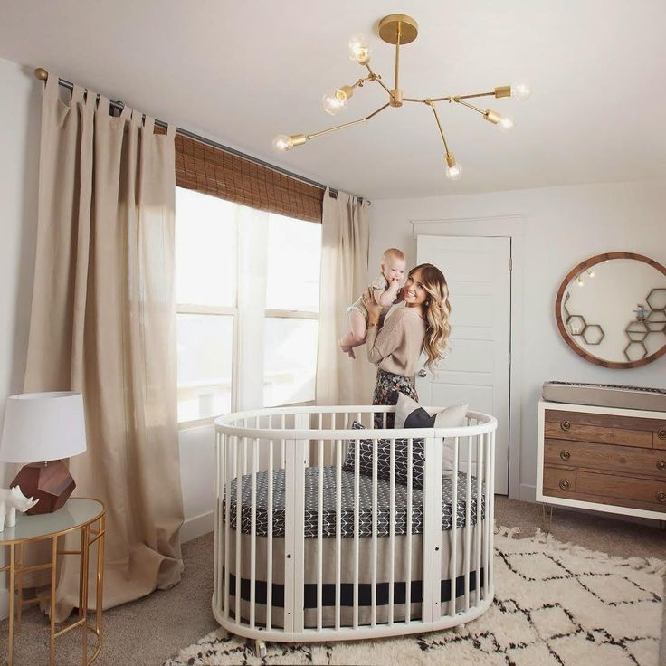 For boy or girl, this neutral modern nursery's centerpiece is the Stokke®  Sleepi oval crib.