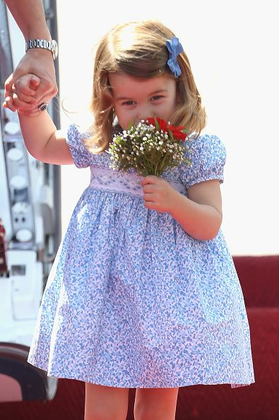 Princess Charlotte of Cambridge smells the flowers she arrives at Berlin Tegel Airport during an official visit to Poland and Germany on July 19, 2017 in Berlin, Germany.