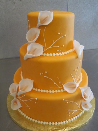 Calla lilies in dark purple, no orange though. Maybe Purple or white faded to purple for the cake with turquoise beads.