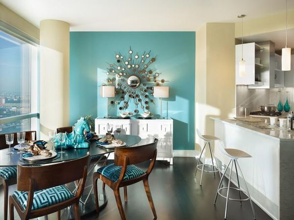 A turquoise accent wall with an oversized sunburst mirror is the focal point of this tropical, midcentury apartment. Design by Gacek Design Group