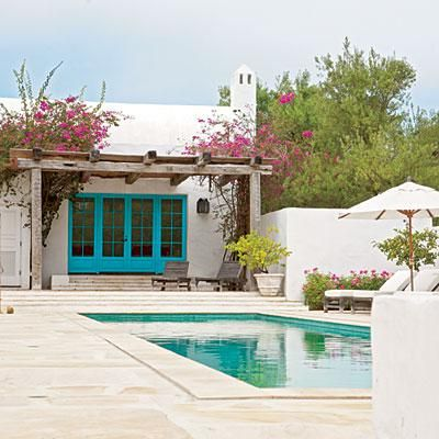 Bright turquoise doors and pink flowers pair with the sea green pool. Coastalliving.com