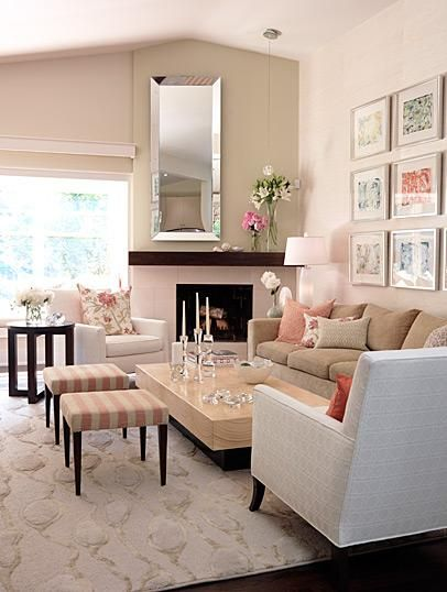 Sarah Richardsonpretty pastel living room design with beveled wall mirror, fireplace, photo art gallery, beige sofa, white geometric chair, striped pink ivory walnut stools, modern wood coffee table, floral pink white beige throw pillows, wool rug, glass accents and glass top accent table. white beige brown pink living room colors.