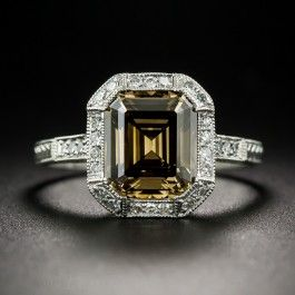 An enchanting emerald-cut diamond, weighing 2.67 carats, imbued with a dusky cognac colored hue, is classically presented in a newly made Art Deco inspired mounting hand-fabricated in platinum. The richly colored diamond, graded Natural Fancy Dark Brown, Even Color, SI2 clarity, by the GIA, is framed with small single-cut diamonds that continue down the shoulders. Intricate, thorough hand engraving adds the finishing touch to this unique, exotic and sophisticated jewel.