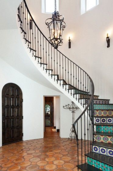 Escaleras clásicas con pasamanos de hierro decorativo, en este caso cada contrapaso se ha aplicado cerámica de diseños geométricos de múltiples colores (Cason Graye Homes).