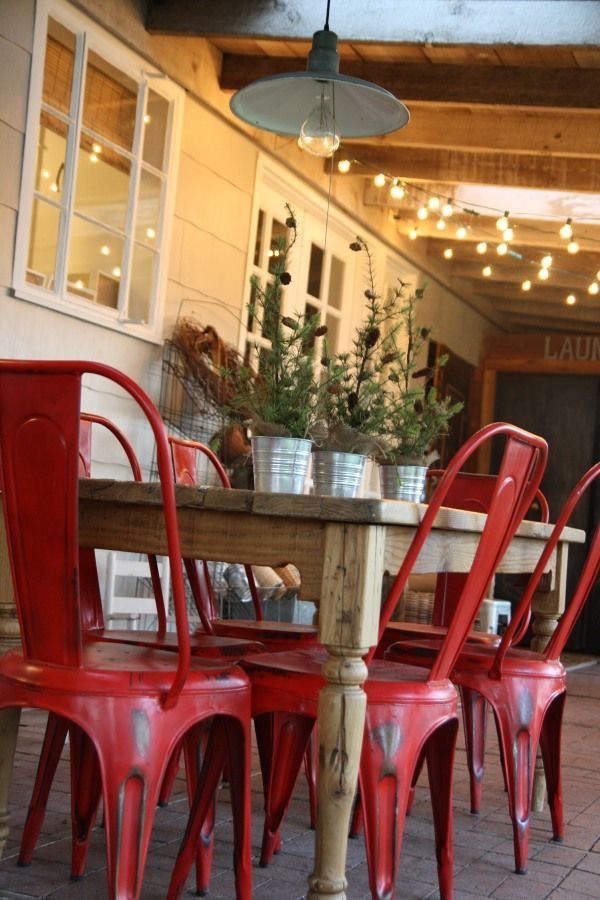 Honey colored farm table with red distressed bistro chairs. Set outdoors on covered patio with string lights and barn pendant.