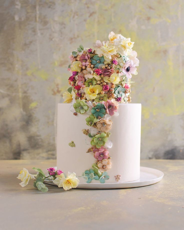 "Gorgeous Floral Wedding Cakes by Maggie Austin | Martha Stewart Weddings: Vintage Enameled Floral Appliqué - ""This cake is packed with little embellishments, including stylized flowers, molded bees, and tiny balls of nonpareils that look like beaded buttons, all nestled together in clusters. I applied them using piping gel in a loose, somewhat random fashion. For this look of overabundance, avoiding symmetry is key."""