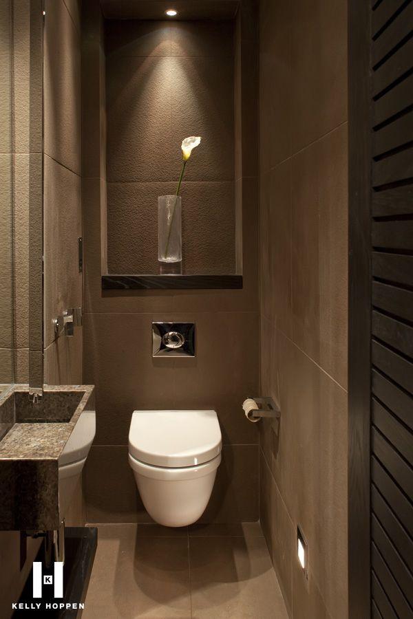 Este es un baño muy moderno y con las paredes marrones.Tiene un váter en el centro. A la izquierda hay un lavabo muy pequeño y sobre del váter hay un especo bastante grande.
