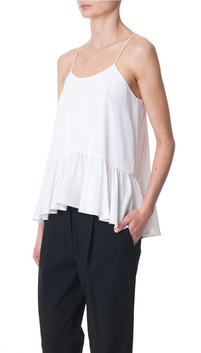 Our signature ruffle peplum camisole has earned its place in the Essentials collection for its year round versatility.  Wear it season after season on its own, or layered under blazers and jackets during cooler months.  Pair with slim pants and pencil skirts for a modern silhouette that flatters all figures. Unlined. Fabrication: 100% Silk. Dry Clean Only.    White Silk Strappy Ruffle Cami styled with Ibis Easy Track Pant and Mina Sandal.  Style number: T0000SHS73279