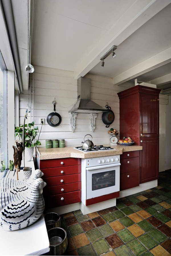 Rode landelijke keuken met gekleurde tegels op de vloer