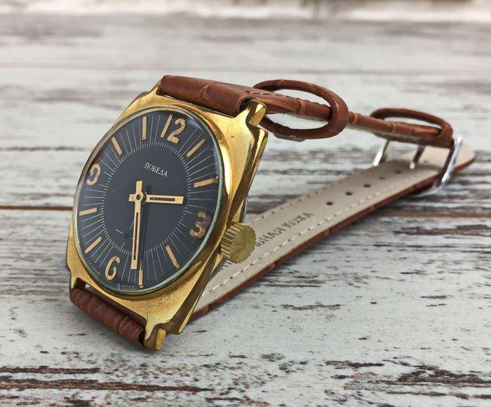 """Pobeda - herenpolshorloge - Jaren 80 - Sovjet-Unie  Russische mannen horloge Pobeda. Zeer goede cosmetische conditie.Heeft de prachtige zwarte wijzerplaat en het glas is zonder krassen.Werkt prima en houdt de juiste tijd. Het horloge is volledig onderhouden gereinigd en geolied. Case vergulde diameter van 33 сm zonder de kroon. De totale lengte van het horloge zaak en de band heeft een 26 cm.""""Pobeda"""" ( """"Overwinning"""") horloges werden gemaakt door de eerste Moscow Watch Factory Kirov na de…"""