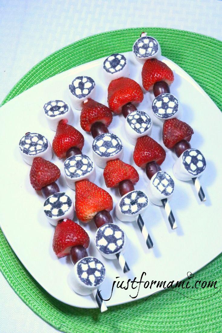 Unos pinchos de fruta con angelitos o marshmalows decorados como pelota de futbol con marcador de tinta comestible con fruta, en este caso fresas y uvas para tu fiesta de futbol soccer o la hora del partido.