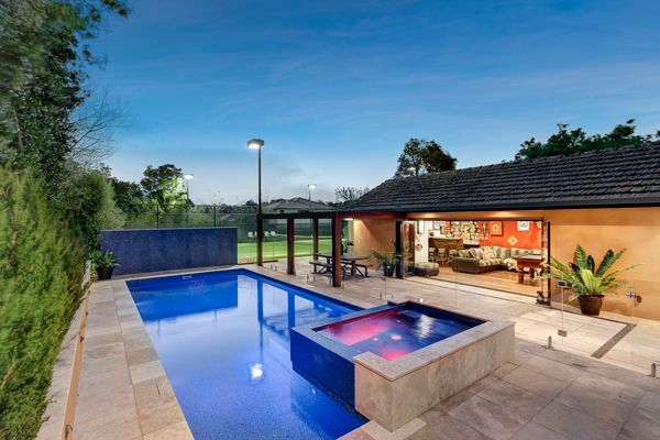 Rectangle pool design featuring an elevated tiled spa and a lap lane alongside, ideal for entertaining and swim fitness. The swimming pool features a rich blue pool colour and is surrounded by travertine tiles.