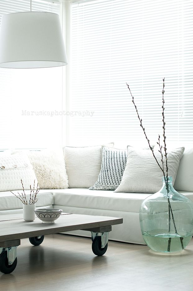"""Oversize decor and furniture pieces - when well selected! - always bring a sense of calm and peaceful reassurance to the space. Look how beautiful this space looks and feels! Notice the big pendant and huge glass   vase """"embracing"""" the space. Also love the low coffee table on wheels, lovely!"""