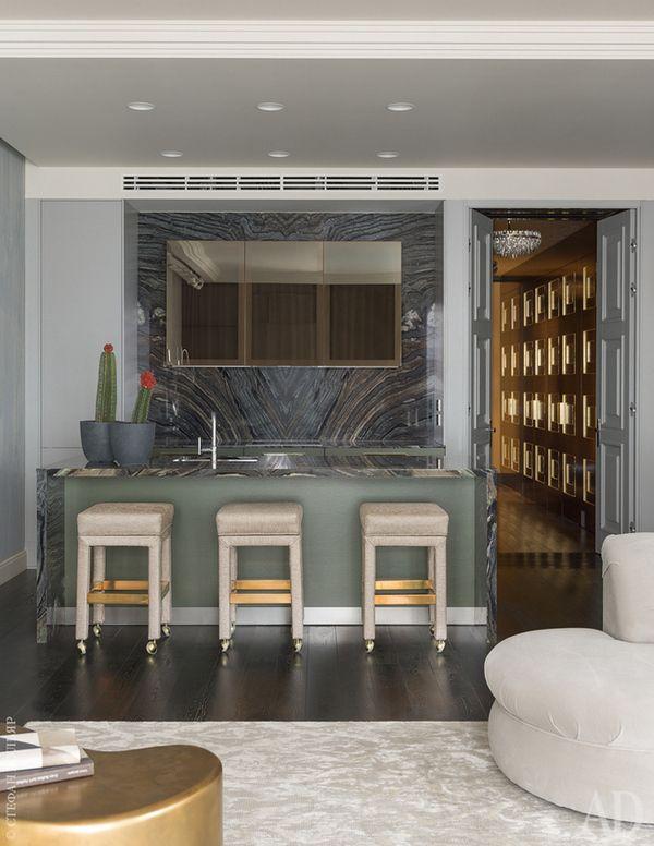 Кухня объединена с гостиной. Кухонная мебель, Leicht, верхние шкафы с зеркальными панелями бронзового оттенка, Varenna. Винтажные барные стулья конца XX века по дизайну Мило Баугмана.