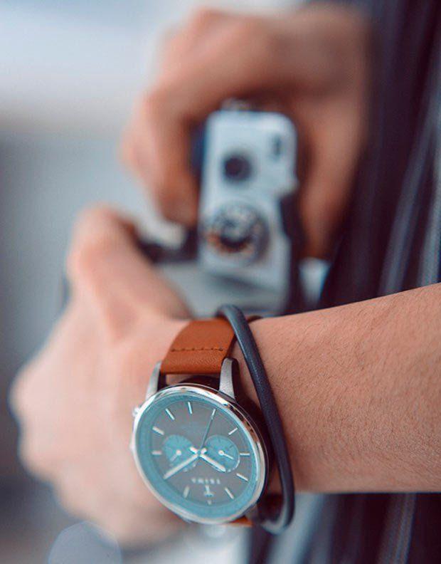 Relógio grande com pulseira de couro marrom.