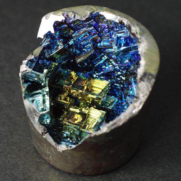 きらびやかな色をまとった、古代都市の発掘を思わせるこの鉱物はビスマスの人工結晶である。天然のビスマスは鉛に似た地味な灰色の塊であるが、溶解し再結晶させると表面に酸化皮膜が発生することにより、大変美しい