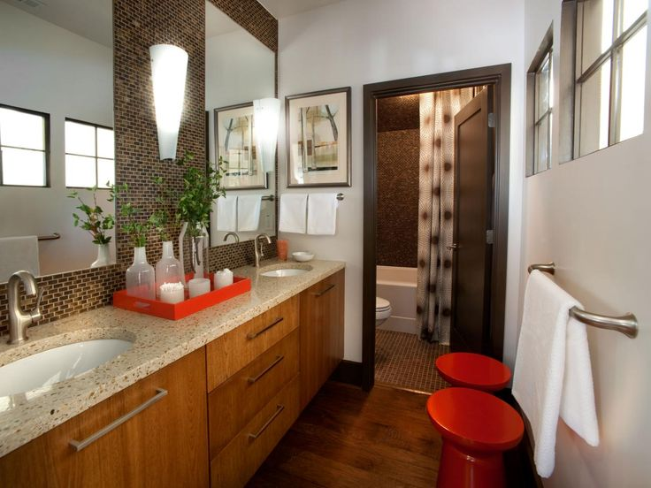 Brown mosaic tile serves as a springboard for this bathroom's casual-chic design sensibility, while twin mirrors visually widen the space. The guest bathroom, from the 2012 HGTV Green Home, has beautifully finished wood cabinets and floors to warm up the room and red accents add a bright pop of color against white walls. The signature tile is a frosted glass micro-block in a tortoise shell-inspired shade. The upper-floor space also features interior windows opening to the adjacent tairwell.