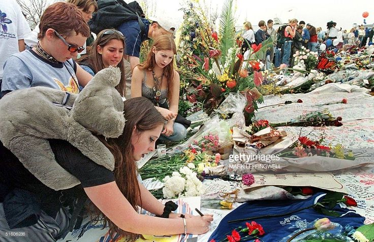 Amber Johnson (L front) writes a note for the Columbine High School shooting victims