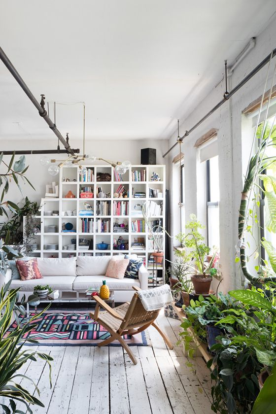 We love the way this room is organized! The grid shelf holds so much without making the room cluttered and the various plants and touches of color throughout the room.