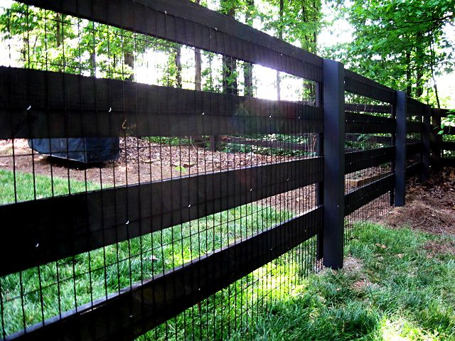 rough sawn wood 4 rail fence stained black with attached wire fence