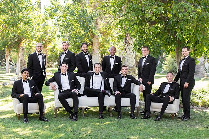 Modern palm springs wedding groom and groomsmen black tuxedo with white dress shirt and black bow tie with black suspenders and white pocket square sitting on couch, bride and groom on couch for summer garden wedding