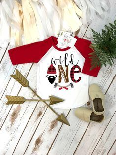 Buffalo Plaid Party, Wild One Birthday Shirt. This adorable Lumberjack Theme Birthday Boy design features a black beard with a lumberjack beanie and buffalo plaid accents and some lumberjack axes. The words read Wild One This is such an adorable shirt for your little mans birthday