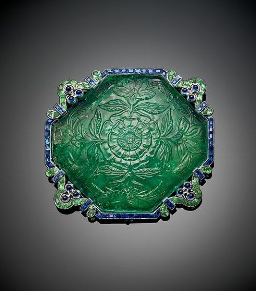 COLLECTION OF SHEIKH HAMAD BIN ABDULLAH AL-THANI -  A brooch featuring a carved emerald bordered by calibré-cut emerald and sapphire in a stylized platinum setting by Cartier, circa 1920. The Al-Thani Collection. (Photo: © Prudence Cuming Associates)