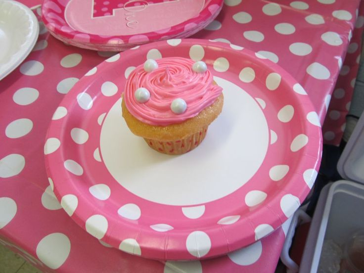 """Throwing a one-derful first birthday bash that's pretty in pink? Deck out your party table with goodies in this girly hue. We recommend cupcakes as they make a delicious and easy finger food treat that everyone enjoys. Frost each cupcake with pink icing and then sprinkle on a few """"pearl"""" candies for an elegant look."""