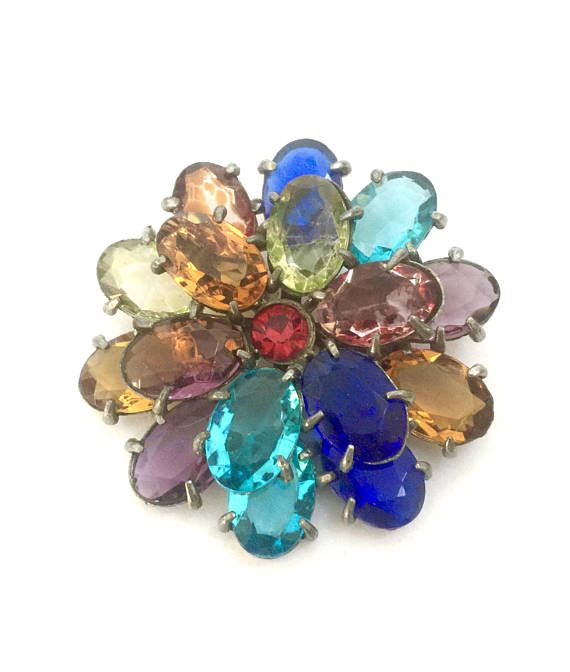 Fruit Salad Layered Flower Brooch  Art Deco style multi-color rhinestone brooch  - Beautiful large flower brooch, measures 2 3/8  - Great colors of large oval rhinestones  - Pot metal silver tone setting  - Very pretty unsigned vintage statement brooch in Good vintage condition, one topaz color stone has lost some color, and there is light age to the metal, primarily on the back of this pretty pin   Please do keep in mind that any vintage and/or antique merchandise may have some deg...