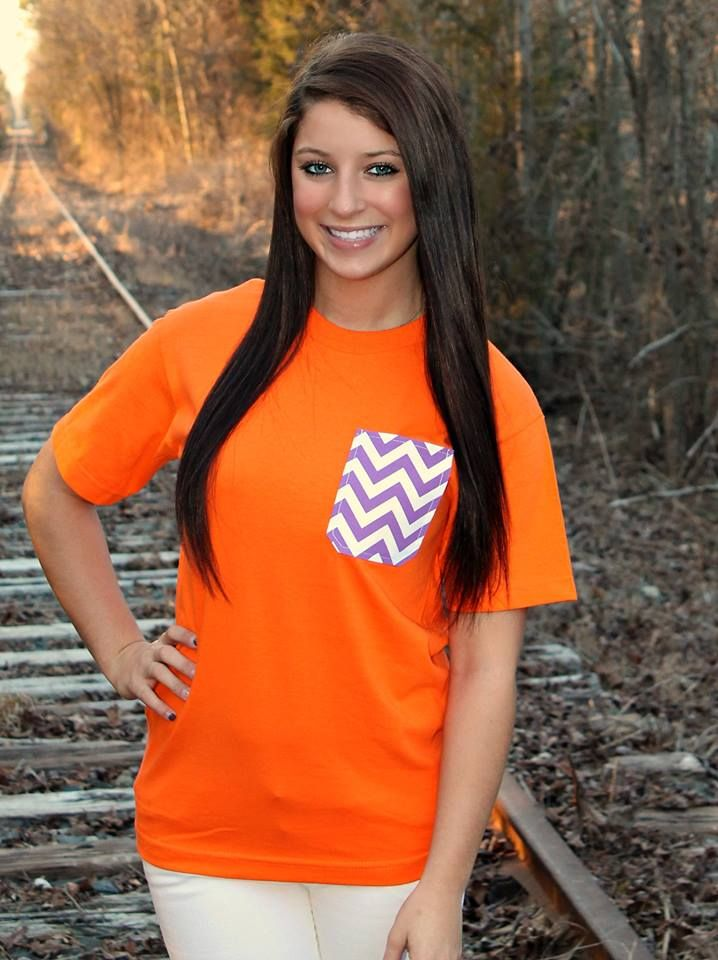 """NEW ARRIVAL! Pocket Tees - Orange $20.99 Real Pocket Tees!! Orange Tee with purple chevron pocket.100% Cotton. Model is wearing a small. She is 5'3"""" & usually wears 2-4.  CLICK BELOW TO ORDER!  ---------------------------------> https://www.southernfriedchics.com/pocket_tee_orange_p/1818-purpzig-orng.htm"""