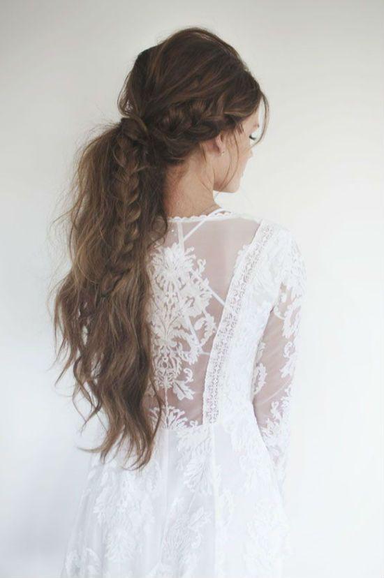 Pour clore cette sélection, on adore cette coiffure un peu floue et romantique ! Les cheveux sont noués bas sur la nuque, et quelques mèches s'échappent. Ils sont très longs, légèrement ondulés, presque emmêlés. Le petit plus ? Une grande tresse sur le côté droit part du haut de la tête jusqu'au milieu du dos et vient se fondre dans la queue de cheval. Voilà une coiffure idéale pour un look bohème, pour compléter cette robe de mariée aux manches longues, à la dentelle joliment travaillée.