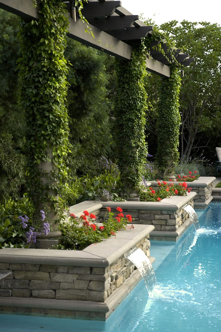 poolside vine-covered pillars with water pouring into pool