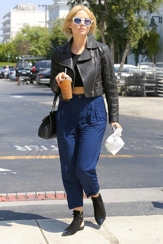 Ashley Benson wears a crop top, cropped moto jacket, high-waisted trousers, and ankle boots
