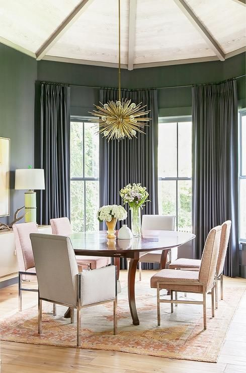 Gray and pink dining room features a vaulted ceiling accented with a brass sputnik chandelier, Arteriors Zanadoo Pendant, illuminating an oval dining table lined with pink velvet dining chairs placed atop an orange and pink rug placed in front of bay windows dressed in dark gray curtains.