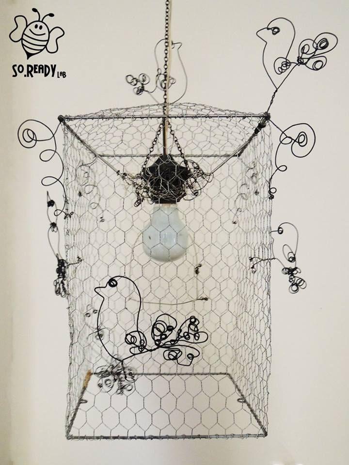 Un lampadario da soffitto, che evoca libertà e romanticismo. Realizzato con una rete metallica, modellata come una gabbia, su cui cinguettano armoniosi uccellini, in fil di ferro, fatti a mano insieme alle volute che decorano gli angoli. Tre piccoli campanellini arricchiscono le volute e la porticina decorativa. #ecodesign #riciclo #soreadystyle - di So.Ready Lab - soreadylab.etsy.com