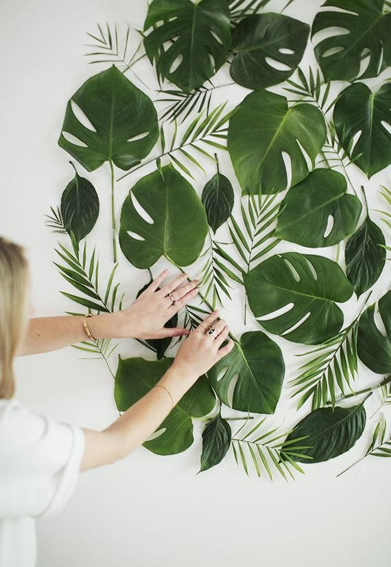 leaves and ferns taped to wall in circular shape for wall art behind wedding welcome table @myweddingdotcom