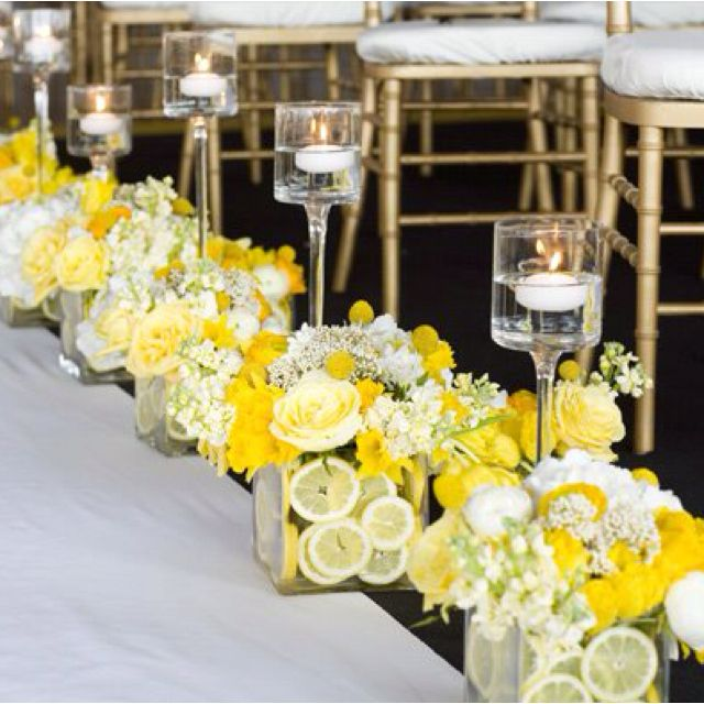 Lemons in a square vase or big mason jar with sunflowers and then a tall vase for a floating votive candle