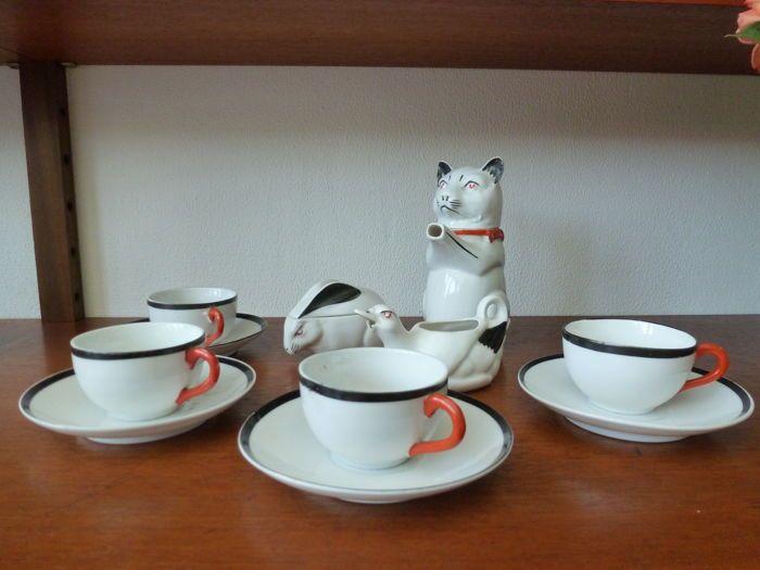 Mosa - 12-Delig aardewerk kinderservies in de vorm van dierfiguren  Prachtig Art Deco kinderserviesje gemaakt door Mosa Porselein uit Maastricht.Het beroemde theeserviesje bestaat uit een theepot melkkannetje suikerpot en 4 kopjes met 5 schotels.De parmantige kat met zijn rode vlinderstrikje is in mooie staat evenals het suikerpotje in de vorm van een konijn.Het melkkannetje in de vorm van een eend heeft een beschadiging aan de onderzijde van de snavel (zie foto's)De kop en schotels zijn…