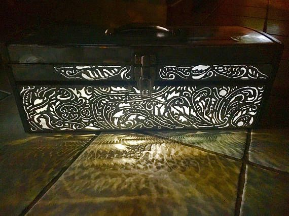This tool box was cut using a plasma torch and the design was taken from an old shotgun engraving. The paint has been taken off on the top and front to making it shine. Lit by LED lights on the inside top Of the lid activated by a button. Original metal handle and latch. -8 1/2 inches