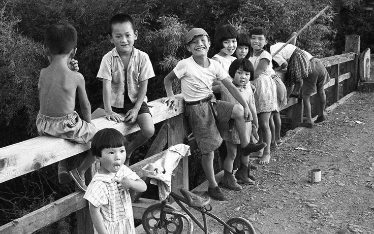 夏休み1. Japanese children in western clothing playing on a bridge. Vintage black and white photograph.