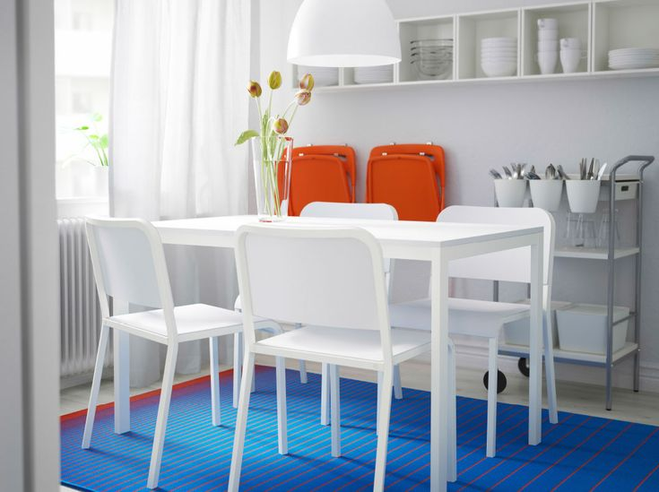 A small dining room with MELLTORP table and chairs in white, orange NISSE foldable chairs and blue MEJLBY rug.